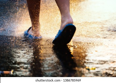 Low angle view of asian boy walking under the rain with colorful sunset light.