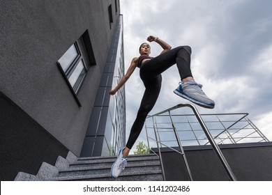 low angle view of asian sportswoman jumping from stairs at urban street
