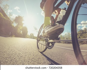 Low angle view of an athlete pushing on the pedals of a racing bicycle during a sport competition. Backlit shot with lens flare.