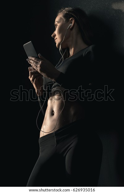 Low angle view of athletic young woman in sportswear using smartphone