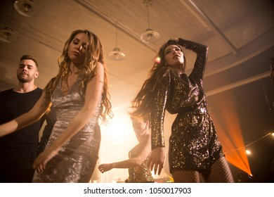 Low angle view of attractive young women wearing trendy dresses enjoying party at night club and dancing to music, male and female silhouettes on background