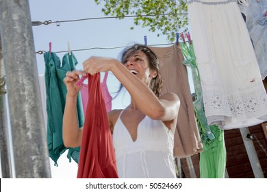 Low angle view of an attractive young woman hanging laundry to dry on a clothesline. Horizontal format.