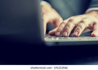 Low angle view from the back of the computer of a businessman typing on a laptop computer keyboard in a retro vintage toned image.