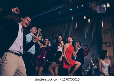 Low angle view of beautiful charming graceful vogue elegant slim cheerful ecstatic glad ladies and trendy funny gentlemen in formal-wear, corporate company event, chill out at fasionable night club