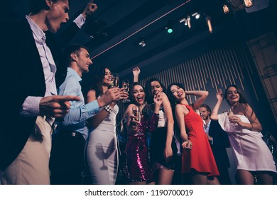 Low angle view of beautiful charming graceful elegant cheerful glad ladies and trendy gentlemen in formal-wear, corporate company event, live band concert, chill out at fasionable night club