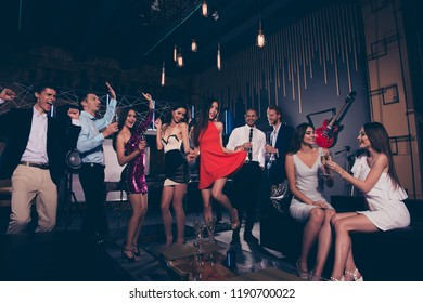 Low angle view of beautiful charming graceful vogue exquisite elegant cheerful ladies and trendy gentlemen in formal-wear, corporate company event, chill out at fasionable night club, gathering