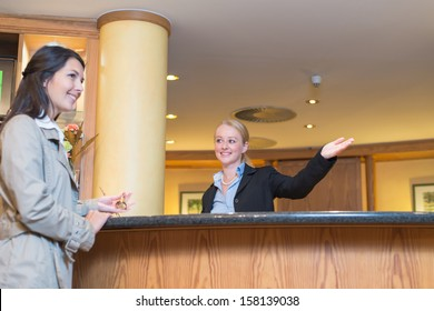 Low angle view of a beautiful friendly smiling receptionist behind the service desk in a hotel lobby helping an attractive female guest indicating with her hand the way to her accomodation