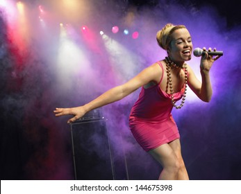 Low angle view of a beautiful young woman singing into microphone on stage