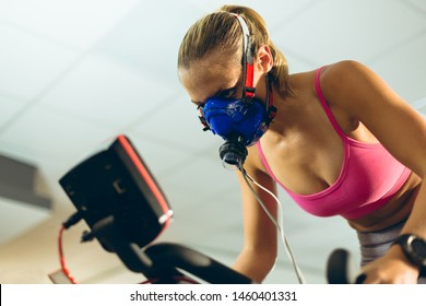Low angle view of beautiful young Caucasian female athlete with oxygen mask exercising with exercise bike in fitness studio. Bright modern gym with fit healthy people working out and training