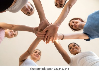 Low angle view from below diverse attractive females putting stacked hands together showing respect unity and friendship. Pretty girls wearing sportswear gathered in sports club for morning training
