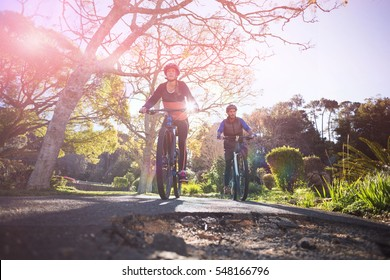 Low angle view of biker couple cycling on countryside road