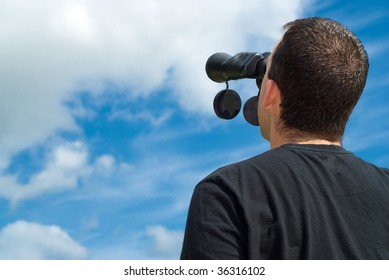Low angle view of a bird watcher using binoculars with some blue sky and clouds behind him