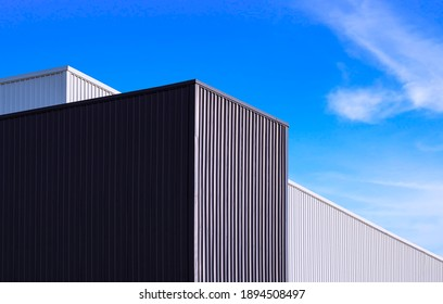 Low angle view of black and white corrugated metal factory buildings against blue sky background