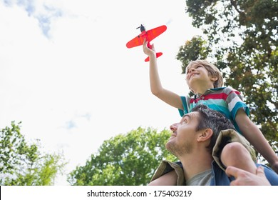 Low angle view of a boy with toy aeroplane sitting on father's shoulders at the park
