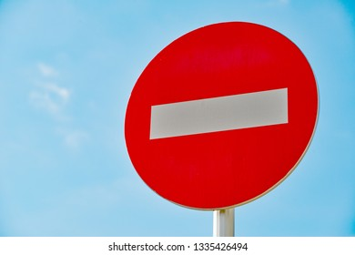 Low angle view of a bright red NO ENTRY roadside sign on a pole, against a clear blue sky background.