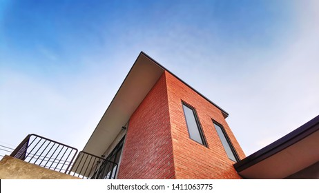 Low Angle View of Building with Balcony Decorated with Bricks Against Blue Sky