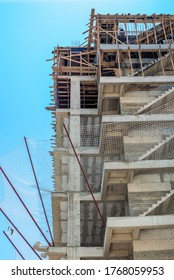 Low angle view of a building under construction with unfinished concrete staircases and construction site safety net which can sustain heavy jerks.