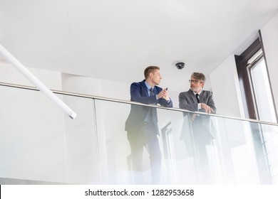 Low angle view of business colleagues discussing while leaning on railing at office