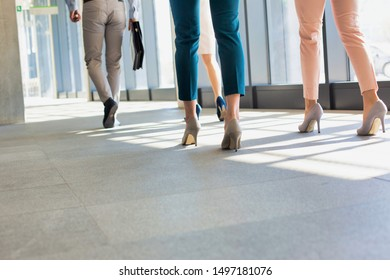 Low angle view of business people walking in office hall