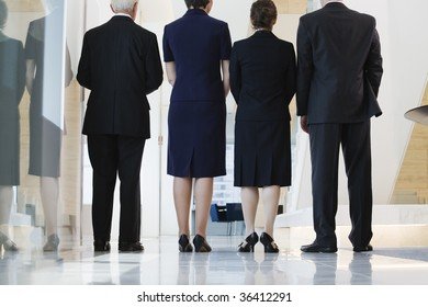 Low angle view of businesspeople standing in a corridor.