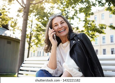 Low angle view of cheerful beautiful European female in her fifties enjoying nice summer weather outdoors, receiving good positive news while having phone conversation, smiling broadly, laughing