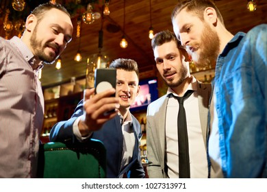 Low angle view of cheerful friends looking through funny photos on smartphone while spending evening in modern pub