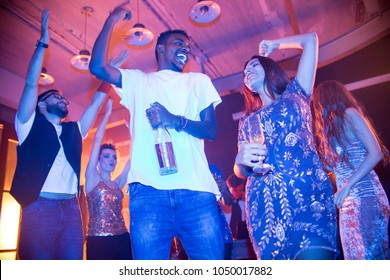 Low angle view of cheerful friends standing in circle at modern night club and dancing with raised hands, multi-ethnic couple with alcoholic drinks on foreground