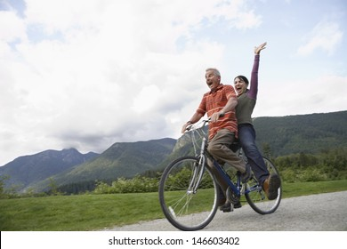 Low angle view of a cheerful middle aged couple riding bicycle on country road