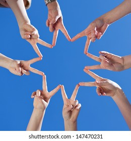 Low angle view of childrens hands forming a star with their fingers touching to the form the points against a clear blue sky, conceptual of teamwork and hope
