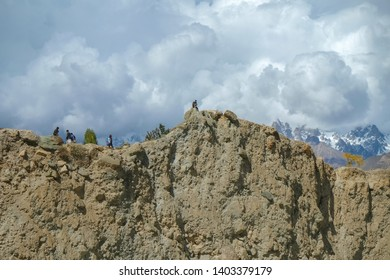 Low angle view of the cliff near the Hopper glacier in Nagar valley with snow capped mountains in karakoram range in the background. Gilgit Baltistan, Pakistan.