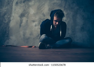 Low angle view close up photo of unhappy unwell troubled tired sick guy sitting on floor suffering from pain ache in body isolated gray background copy space
