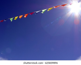 Low angle view of colorful flags against sky with sunspot in Riga, Latvia.