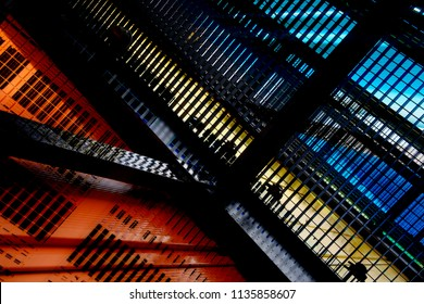 Low angle view of colorful industrial architecture in bright orange, yellow and blue backlight. Abstract architectural composition featuring shiny metal girders, grid structures and louvered walls.