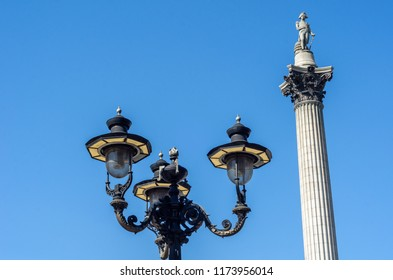 Low angle view of Nelson's Column and streetlights at Trafalgar Square in London, England. It's a monument to Admiral Horatio Nelson who died at the Battle of Trafalgar during the Napoleonic Wars