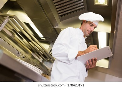 Low angle view of a concentrated male cook writing on clipboard in the kitchen