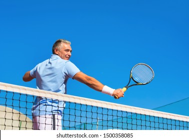 Low angle view of confident mature man hitting tennis ball with racket on court against clear blue sky