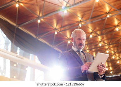 Low angle view of confident senior businessman using digital tablet while standing against illuminated roof