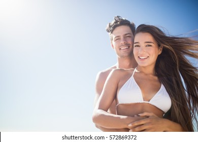 Low angle view of couple embracing on the beach