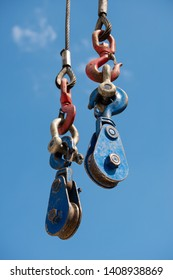 Low angle view of a crane hook and pulley system against a clear blue sky.