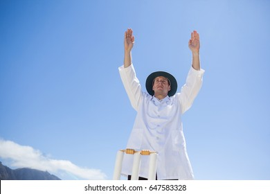 Low angle view of cricket umpire signalling six while standing against sky at match
