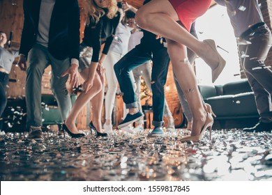 Low angle view cropped close-up photo of legs girls guys meeting rejoicing dance floor x-mas party glitter flying air wear formalwear high heels red dress silver skirt pants restaurant indoors