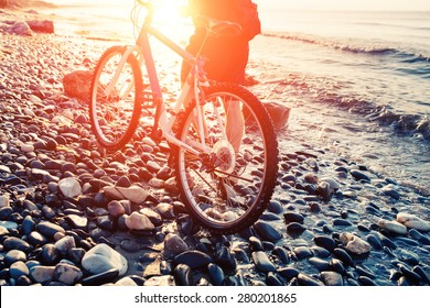 Low angle view of cyclist holding his bike. Man with bicycle on a sea shore sunset. Pebble beach coast.