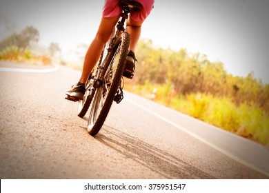 low angle view of cyclist riding mountain bike on public road