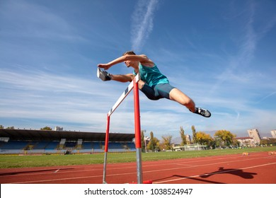 Low angle view of determined male athlete jumping over a hurdles