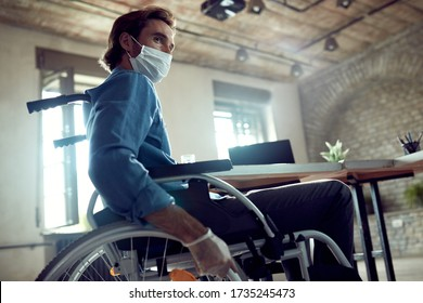 Low angle view of disabled businessman in wheelchair wearing face mask while working in the office during coronavirus epidemic.