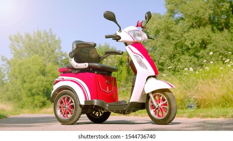 Low angle view of electric scooter on the road. Red stylish e vehicle. Environmentally  conscious transportation parked in the green city park. Environmentally conscious travel choices.