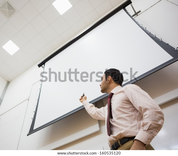 Low angle view of an elegant male teacher with projection screen in the lecture hall