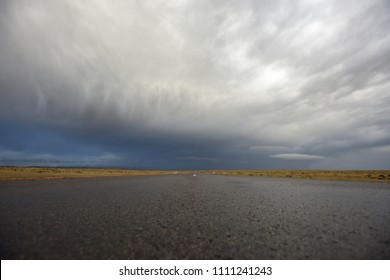 Low angle view of empty asphalt road under stormy dramatic sky. Copy space for text or product