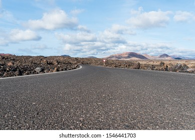 low angle view of empty asphalt road road through arid volcanic landscape against blue sky