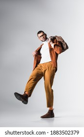 Low angle view of fashionable man holding brown bag and looking at camera on grey background